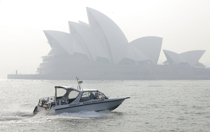A water taxis drives by as smoke haze hangs over the Sydney Opera House in Sydney, Thursday, Nov. 21, 2019. The annual Australian fire season, which peaks during the Southern Hemisphere summer, has started early after an unusually warm and dry winter. (AP Photo/Rick Rycroft)