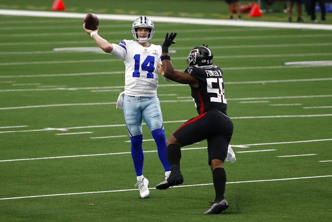 Dallas Cowboys quarterback Andy Dalton (14) throws a pass under pressure from Atlanta Falcons defensive end Dante Fowler Jr. (56) in the second half of an NFL football game in Arlington, Texas, Sunday, Sept. 20, 2020. (AP Photo/Ron Jenkins)