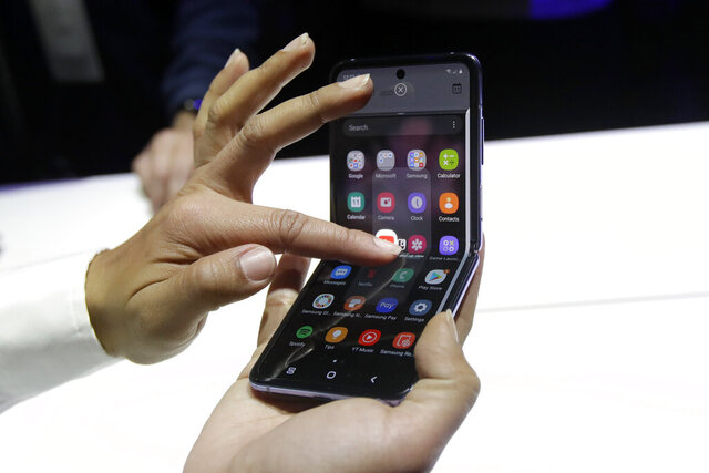 A Samsung worker gives a demonstration of the Galaxy Z Flip Phone at the Unpacked 2020 event in San Francisco, Tuesday, Feb. 11, 2020. (AP Photo/Jeff Chiu)