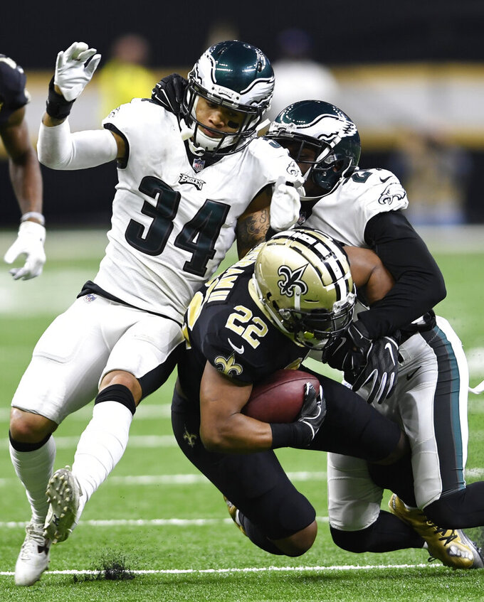 New Orleans Saints running back Mark Ingram (22) is hit by Philadelphia Eagles cornerback Cre'von LeBlanc (34) in the second half of an NFL divisional playoff football game in New Orleans, Sunday, Jan. 13, 2019. (AP Photo/Bill Feig)