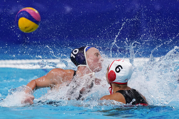 Canada's Gurpreet Sohi (6) shoots over the reach of United States' Kaleigh Gilchrist, left, during a quarterfinal round women's water polo match at the 2020 Summer Olympics, Tuesday, Aug. 3, 2021, in Tokyo, Japan. (AP Photo/Mark Humphrey)