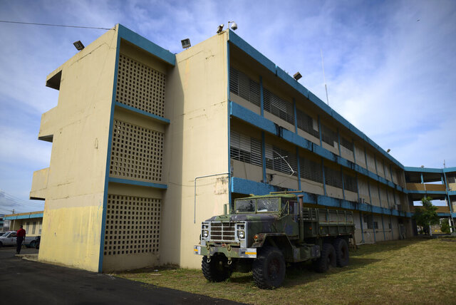 An old military truck used during flooding sits parked at the Carlos Escobar Lopez vocational school which will be used as a shelter during this year's hurricane season in Loiza, Puerto Rico, Thursday, May 28, 2020. Caribbean islands have rarely been so vulnerable as an unusually active hurricane season threatens a region still recovering from recent storms as it fights a worsening drought and a pandemic that has drained budgets and muddled preparations.  (AP Photo/Carlos Giusti)