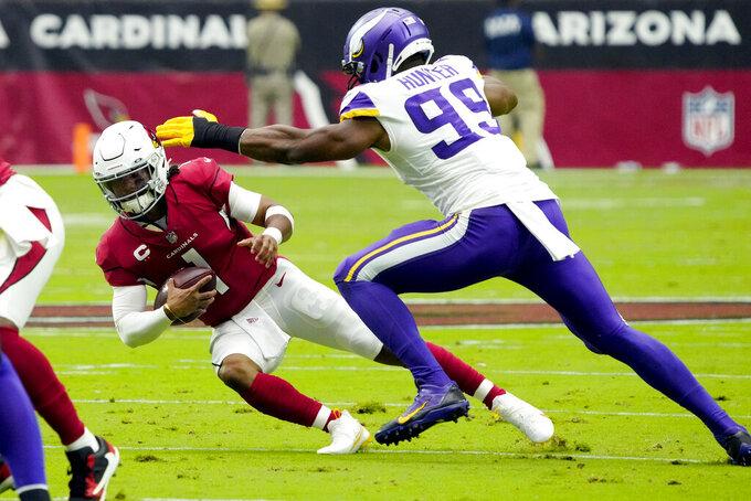 Arizona Cardinals quarterback Kyler Murray (1) avoids the tackle of Minnesota Vikings defensive end Danielle Hunter (99) during the first half of an NFL football game, Sunday, Sept. 19, 2021, in Glendale, Ariz. (AP Photo/Rick Scuteri)