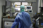 FILE - In this Monday, March 16, 2020 file photo, a doctor watches a coronavirus patient under treatment in the intensive care unit of the Brescia hospital, Italy. Amid the chaos of the pandemic's early days, doctors who faced the first COVID-19 onslaught reached across oceans and language barriers in an unprecedented effort to advise colleagues trying to save lives. (AP Photo/Luca Bruno)