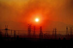FILE - In this Oct. 11, 2019, file photo, smoke from a wildfire called the Saddle Ridge Fire hangs above power lines as the sun rises in Newhall, Calif. Thousands of people in Southern California lost power Thanksgiving Day after a utility began shutting off electricity to prevent wildfires from being ignited by damage to power lines amid strong winds. At least 3,000 customers in Los Angeles and Ventura counties lost electricity Thursday, Nov. 26, 2020 and more than 100,000 other customers are at risk of losing power, according to Southern Edison. (AP Photo/Noah Berger, File)