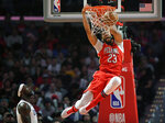 FILE - In this April 9, 2018, file photo, New Orleans Pelicans forward Anthony Davis dunks as Los Angeles Clippers forward Montrezl Harrell watches during the second half of an NBA basketball game, in Los Angeles.  Only a few hours remain to determine if the Anthony Davis saga ends for this season or lingers into the summer. The NBA trade deadline is Thursday, Feb. 7, 2019, at 3 p.m. EST, and Davis is still seeking a trade from the New Orleans Pelicans.(AP Photo/Mark J. Terrill, File)