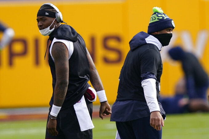 Washington Football Team quarterback Dwayne Haskins, left, and Seattle Seahawks quarterback Russell Wilson, walking past each other before the start of an NFL football game, Sunday, Dec. 20, 2020, in Landover, Md. (AP Photo/Susan Walsh)