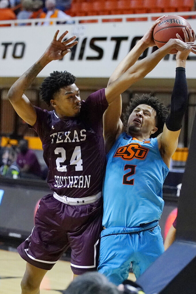 Oklahoma State guard Cade Cunningham (2) shoots next to Texas Southern forward John Walker III (24) during the second half of an NCAA college basketball game in Stillwater, Okla., Saturday, Nov. 28, 2020. (AP Photo/Sue Ogrocki)