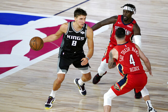 Sacramento Kings' Bogdan Bogdanovic (8) drives against New Orleans Pelicans' Jrue Holiday, back right, and JJ Redick (4) during the second half of an NBA basketball game Thursday, Aug. 6, 2020 in Lake Buena Vista, Fla. (AP Photo/Ashley Landis, Pool)