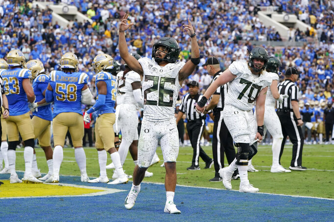 Oregon running back Travis Dye (26) celebrates his rushing touchdown during the first half of an NCAA college football game against UCLA, Saturday, Oct. 23, 2021, in Pasadena, Calif. (AP Photo/Marcio Jose Sanchez)