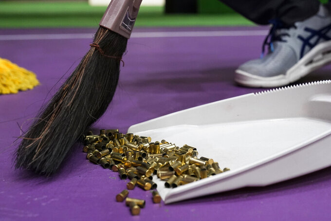 Empty .22 LR caliber shell casings are swept up after the women's 25-meter pistol at the Asaka Shooting Range in the 2020 Summer Olympics, Friday, July 30, 2021, in Tokyo, Japan. (AP Photo/Alex Brandon)
