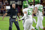 Oregon coach Mario Cristobal greets his team after a touchdown during the first half of an NCAA college football game against Arizona State, Saturday, Nov. 23, 2019, in Tempe, Ariz. (AP Photo/Matt York)