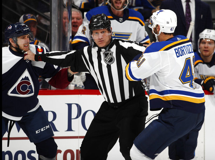 Linesman Greg Devorski, center, separates Colorado Avalanche left wing A.J. Greer, left, and St. Louis Blues defenseman Robert Bortuzzo as they try to fight in the first period of an NHL hockey game Saturday, Feb. 16, 2019, in Denver. Both players were assessed a penalty for their actions. (AP Photo/David Zalubowski)