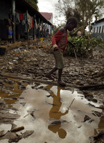 A young boy walks through a muddy walkway in Buzi district, 200 kilometers (120 miles) outside Beira, Mozambique, on Saturday, March 23, 2019. A second week has begun with efforts to find and help some tens of thousands of people in devastated parts of southern Africa, with some hundreds dead and an unknown number of people still missing. (AP Photo/Themba Hadebe)