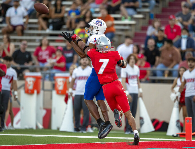 Houston Baptist wide receiver Vernon Harrell, left, reaches to catch a pass defended by New Mexico safety Tavian Combs (7) during the first half of an NCAA college football game on Thursday, Sept. 2, 2021, in Albuquerque, N.M. (AP Photo/Andres Leighton)