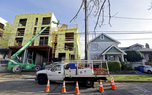 FILE - In this Dec. 13, 2017 file photo, a four-story mixed-use building is under construction adjacent to an older, single-family home in Seattle. A massive influx of new residents and an ensuing housing crunch has led to skyrocketing rents. On Monday, Feb. 10, 2020, the Seattle City Council unanimously approved a ban on evictions during December, January and February. (AP Photo/Elaine Thompson, File)