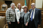 New Washington Supreme Court Chief Justice Debra Stephens, second from left, poses for a photo with former Chief Justices Mary Fairhurst, left, Barbara Madsen, second from right, and Gerry Alexander, right, following a swearing in ceremony, Monday, Jan. 6, 2020, in Olympia, Wash. Stephens replaced Fairhurst as Chief Justice, after Fairhurst retired in January as she battles cancer. (AP Photo/Ted S. Warren)