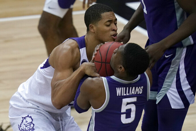 TCU forward Jaedon LeDee, left, ties up Kansas State guard Rudi Williams (5) during the first half of an NCAA college basketball game in the first round of the Big 12 men's tournament in Kansas City, Mo., Wednesday, March 10, 2021. (AP Photo/Orlin Wagner)