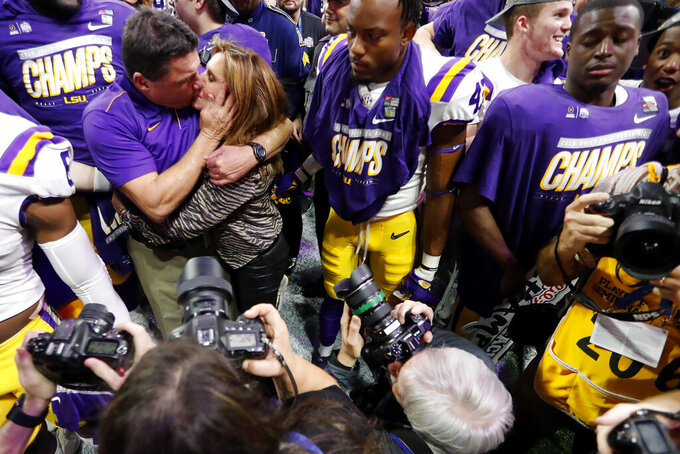 LSU coach Ed Orgeron kisses his wife, Kelly, after the team's Peach Bowl NCAA semifinal college football playoff game against Oklahoma, Saturday, Dec. 28, 2019, in Atlanta. LSU won 63-28. (AP Photo/John Bazemore)