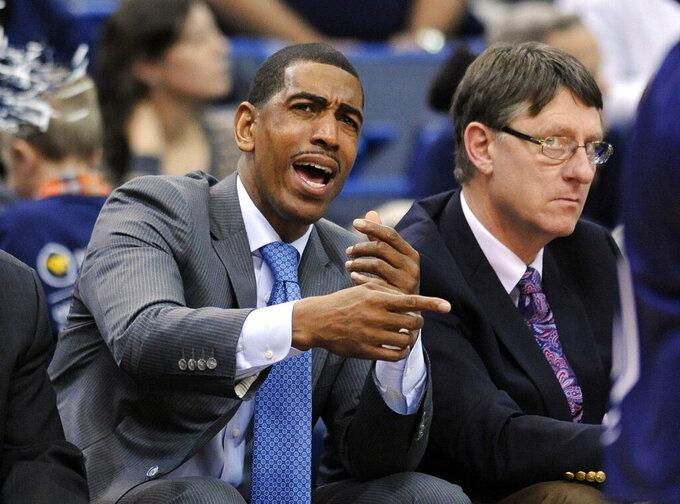 FILE - In this Dec. 6, 2013, file photo, then-Connecticut head coach Kevin Ollie signals to his team as associate head coach Glenn Miller looks on during the first half of Connecticut's 95-68 victory over Maine in an NCAA college basketball game, in Hartford, Conn. Former UConn basketball coach Kevin Ollie has filed a lawsuit against former assistant Glenn Miller, contending Miller slandered him in comments to the NCAA. Miller told the governing body he had learned about an alleged $30,000 payment Ollie made to the mother of a recruit while at UConn. Ollie's lawsuit, filed Monday, April 29, 2019, in Connecticut Superior Court, says that accusation was false and damaged his reputation.  (AP Photo/Fred Beckham, File)