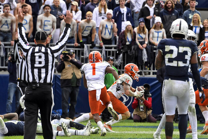 Illinois wide receiver Casey Washington (14) celebrates after catching a pass for a 2-point conversion in the ninth overtime to defeat Penn State 20-18 in an NCAA college football game in State College, Pa.on Saturday, Oct. 23, 2021. (AP Photo/Barry Reeger)
