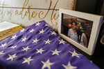 An image of Ana Martinez rests on a table beside an American flag and Christian bible, Thursday, Nov. 26, 2020, in Deer Park, N.Y. COVID-19 claimed the life of the retired seamstress at age 78 on April 1 while she was recovering at a nursing home from a knee replacement. (AP Photo/John Minchillo)