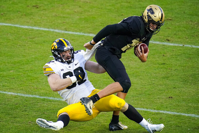 Purdue quarterback Aidan O'Connell (16) escapes from the grasp of Iowa defensive lineman John Waggoner (92) during the third quarter of an NCAA college football game in West Lafayette, Ind., Saturday, Oct. 24, 2020. (AP Photo/Michael Conroy)
