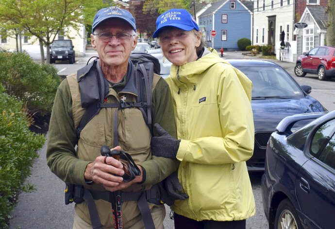 In this Wednesday, May 15, 2019 photo, U.S. Air Force veteran William Shuttlesworth, left, poses with his wife Patty on Market Street, in Newburyport, Mass., at the start of his planned cross-country hike to raise awareness for veterans' issues. Shuttleworth, 71, trained for several months carrying his full backpack while walking several miles each day. (Richard K. Lodge/The Daily News of Newburyport via AP)
