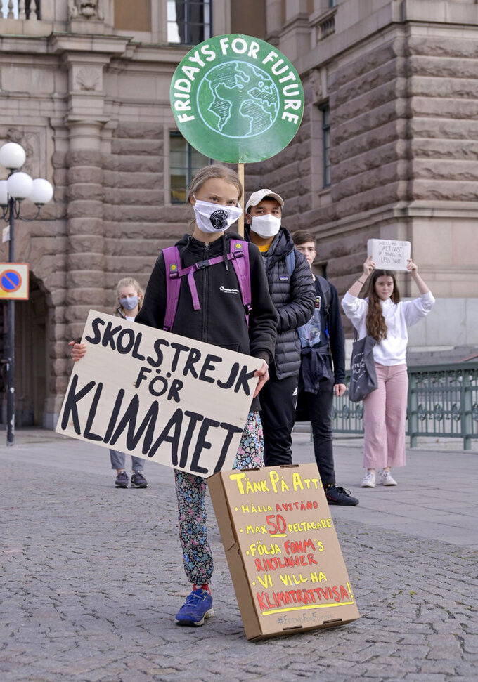 """Swedish climate activist Greta Thunberg, center, holding a sign reading """"School strike for Climate""""and others protest in front of the Swedish Parliament Riksdagen in Stockholm Friday, Sept. 25, 2020. ( Janerik Henriksson/TT News Agency via AP)"""