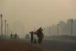 In this Thursday, Nov. 8, 2018, file photo, a municipal worker with her daughter leaves after sweeping the India Gate area as a thick lawyer of pollution haze hangs a day after Diwali festival, in New Delhi, India. Toxic smog shrouds the Indian capital as air quality falls to hazardous levels with tens of thousands of people setting off massive firecrackers to celebrate the major Hindu festival of Diwali on Wednesday night. (AP Photo/Manish Swarup, File)