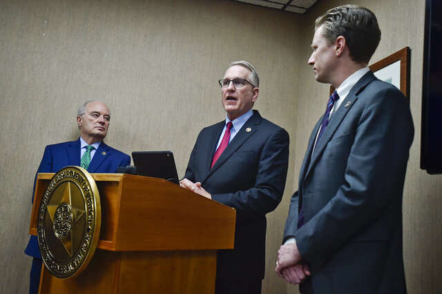 Montana Attorney General Tim Fox, center, announces a lawsuit against the McKesson Corporation and Cardinal Health, Inc., two leading distributors of narcotic opioids, for their alleged role in the opioid crisis, Monday, Feb. 3, 2020, in the Attorney's General's office. in Helena, Mont. Flanking Fox is Jon Bennion, right, Chief Deputy Attorney General, and Mark Mattioli, Consumer Protection Chief, left. (Thom Bridge/Independent Record via AP)