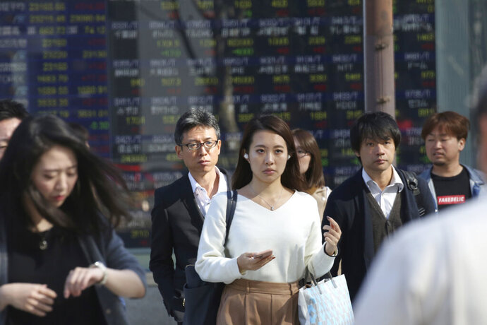 In this Tuesday, Nov. 5, 2019, photo, people walk by an electronic stock board of a securities firm in Tokyo. Asian stock markets were mixed Wednesday, Nov. 6, 2019, after investors were rattled by a possible snag in a U.S.-Chinese trade truce following reports Beijing wants Washington to life punitive tariffs. (AP Photo/Koji Sasahara)