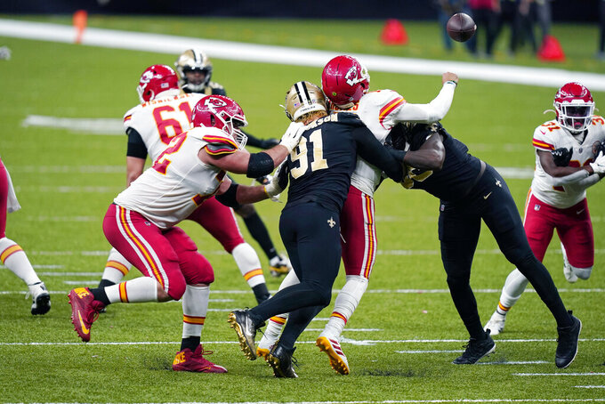 Kansas City Chiefs quarterback Patrick Mahomes (15) fumbles as he is sacked by New Orleans Saints defensive end Trey Hendrickson (91) in the second half of an NFL football game in New Orleans, Sunday, Dec. 20, 2020. (AP Photo/Butch Dill)