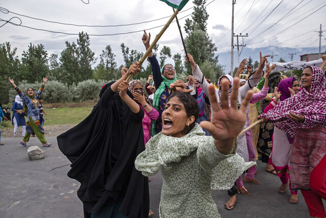 Women shout slogans as Indian policemen fire teargas and live ammunition in the air to stop a protest march in Srinagar, Indian controlled Kashmir, Aug. 9, 2019. The image was part of a series of photographs by Associated Press photographers which won the 2020 Pulitzer Prize for Feature Photography. (AP Photo/Dar Yasin)