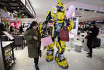 In this Thursday, Feb. 14, 2019, photo, a Transformer's Bumblebee mascot helps a woman carries paper bags at a shopping mall in Handan in north China's Hebei province. U.S. and Chinese envoys are holding a second day of trade talks after the top economic adviser to President Donald Trump said he has yet to decide whether to go ahead with a March 2 tariff increase on imports from China. (Chinatopix via AP)