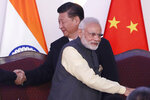 In this Oct. 16, 2016, file photo, Indian Prime Minister Narendra Modi, front and Chinese President Xi Jinping shake hands with leaders at the BRICS summit in Goa, India. Tensions along the China-India border high in the Himalayas have flared again in recent weeks.  Indian officials say the latest row began in early May when Chinese soldiers entered the Indian-controlled territory of Ladakh at three different points, erecting tents and guard posts. (AP Photo/Manish Swarup, File)