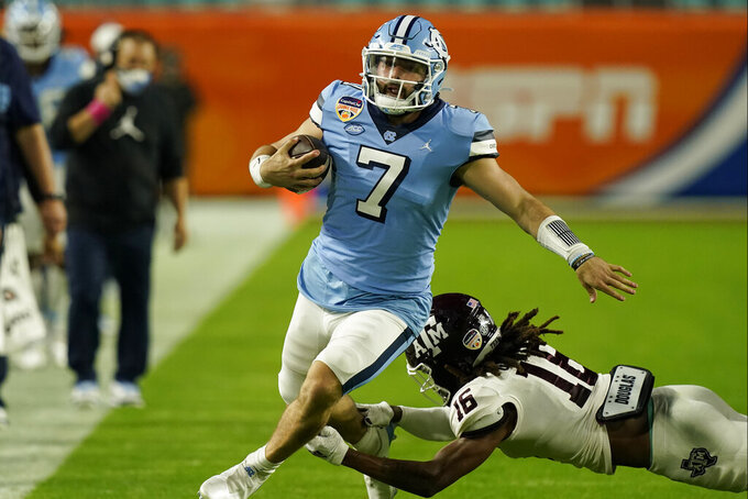 FILE - North Carolina quarterback Sam Howell (7) avoids a tackle by Texas A&M defensive back Brian George (16) during the first half of the Orange Bowl NCAA college football game in Miami Gardens, Fla., in this Saturday, Jan. 2, 2021, file photo. Howell is leading an offense that has major personnel losses. But Howell is back for his junior season as a Heisman Trophy candidate and top NFL prospect, using spring practices to improve timing and chemistry with new starters as the offense takes shape. (AP Photo/Marta Lavandier, File)