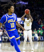 Notre Dame's Temple 'T.J.' Gibbs, right, shoots a 3-pointer near UCLA's Tyger Campbell during the first half of an NCAA college basketball game Saturday, Dec. 14, 2019, in South Bend, Ind. (AP Photo/Robert Franklin)