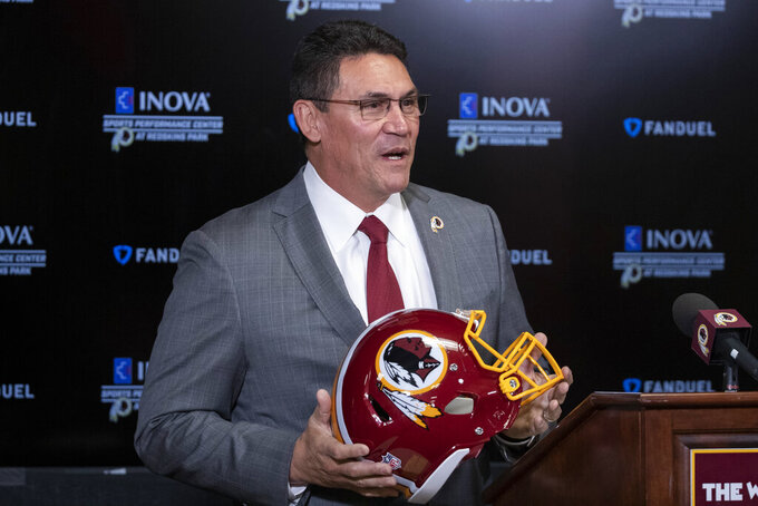 FILE - In this Jan. 2, 2020, file photo, Washington Redskins head coach Ron Rivera holds up a helmet during a news conference at the team's NFL football training facility in Ashburn, Va. A new name must still be selected for the Washington Redskins football team, one of the oldest and most storied teams in the National Football League, and it was unclear how soon that will happen. But for now, arguably the most polarizing name in North American professional sports is gone at a time of reckoning over racial injustice, iconography and racism in the U.S. (AP Photo/Alex Brandon, File)