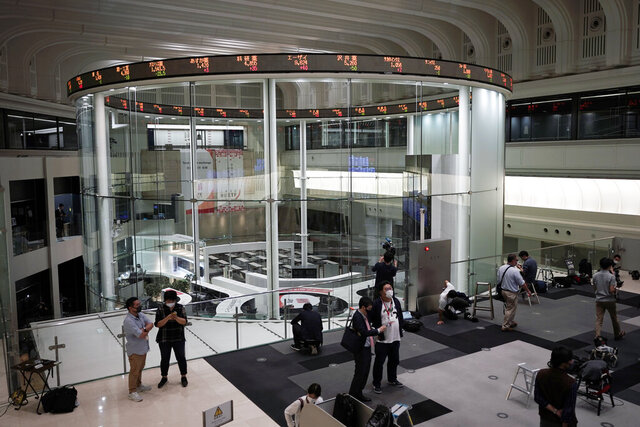 Journalists film an electronic stock board showing reopened Japan's Nikkei 225 index at Tokyo Stock Exchange in Tokyo Friday, Oct. 2, 2020. Tokyo's market resumed trading Friday after a full-day outage due to a malfunction in its computer systems. (AP Photo/Eugene Hoshiko)
