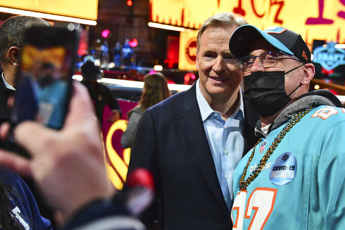 NFL Commissioner Roger Goodell takes photos with fans during the third round of the NFL football draft, Friday, April 30, 2021, in Cleveland. (AP Photo/David Dermer)