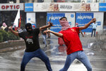Hezbollah supporters and communist groups throw stones at riot police during a protest against U.S. interference in Lebanon's affairs, near the U.S. embassy in Aukar, northeast of Beirut, Lebanon, Friday, July 10, 2020. (AP Photo / Hussein Malla)