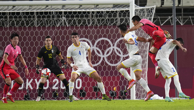 Goalkeeper Marian Aioani of Romania (black) and teammate Alexandru Pascanu look at the ball before an own goal as the come under pressure from South Korea during a men's soccer match at the 2020 Summer Olympics, Sunday, July 25, 2021, in Kashima, Japan. (AP Photo/Fernando Vergara)