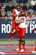 Utah running back TJ Green (4) celebrates with Orlando Umana (50) after scoring a touchdown against Arizona during the second half of an NCAA college football game Saturday, Nov. 23, 2019, in Tucson, Ariz. (AP Photo/Rick Scuteri)