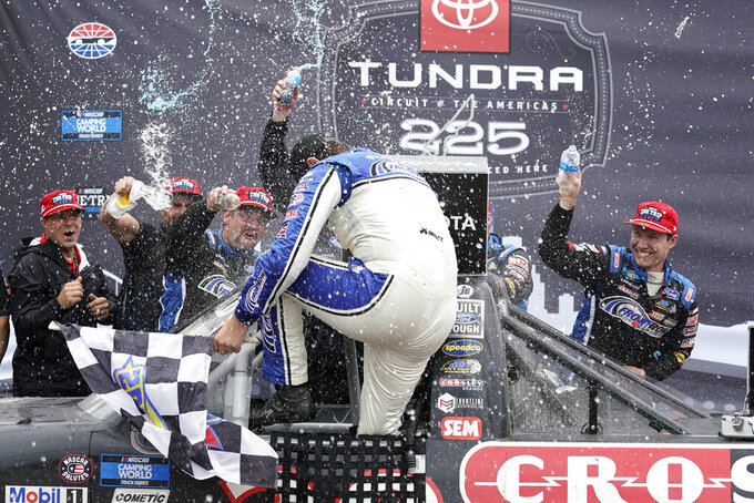 Todd Gilliland celebrates with his crew in Victory Lane after winning the NASCAR Truck Series auto race at the Circuit of the Americas in Austin, Texas, Saturday, May 22, 2021. (AP Photo/Chuck Burton)