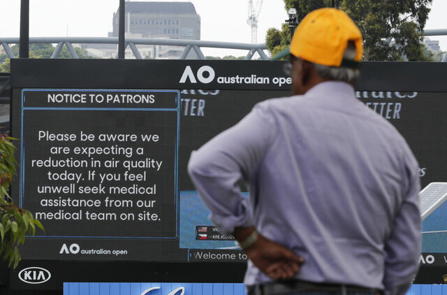 A spectator reads a sign warning of air quality ahead of the Australian Open tennis championship in Melbourne, Australia, Saturday, Jan. 18, 2020. (AP Photo/Lee Jin-man)