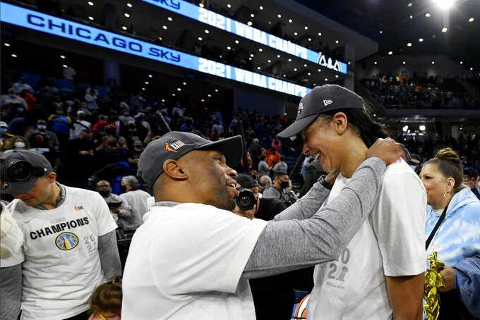 Chicago Sky's Candice Parker right, celebrates with head coach James Wade left, after defeating the Phoenix Mercury in Game 4 of the WNBA Finals to become champions Sunday, Oct. 17, 2021, in Chicago. (AP Photo/Paul Beaty)