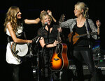 FILE - In this Oct. 18, 2007 file photo, Emily Robison, left, and Martie Maguire, right, adjust Natalie Maines' hair as the Dixie Chicks perform at the new Nokia Theatre in Los Angeles. The Grammy-winning country group have dropped the word dixie from their name and are now going by The Chicks. The move follows a decision by country group Lady Antebellum to change to Lady A after acknowledging the word's association to slavery. (AP Photo/Gus Ruelas, File)