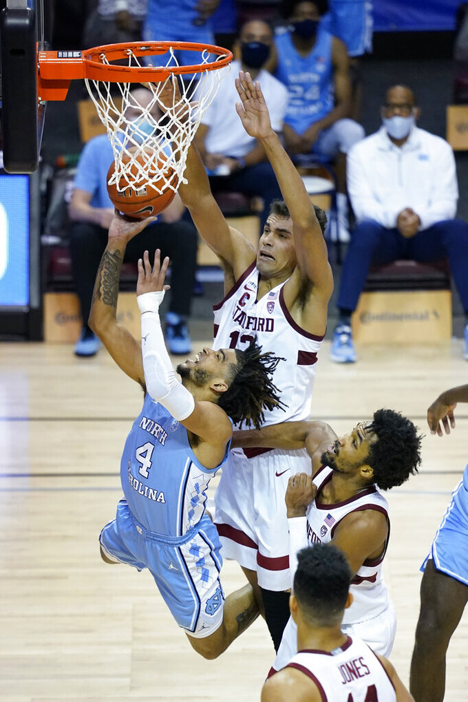 North Carolina guard R.J. Davis (4) leaps to the basket past Stanford forward Oscar da Silva (13) and guard Bryce Wills (2) during the second half of an NCAA college basketball game in the semifinals of the Maui Invitational, Tuesday, Dec. 1, 2020, in Asheville, N.C. (AP Photo/Kathy Kmonicek)