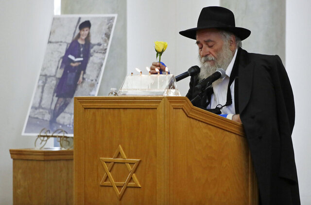 FILE - Yisroel Goldstein, Rabbi of Chabad of Poway, holds a yellow rose as he speaks at the funeral for Lori Gilbert-Kaye, who is pictured at left, in Poway, Calif., Monday, April 29, 2019. Anti-Semitic hate crimes in California rose nearly 12% in 2019 even as hate crimes overall declined statewide by 4.8%, according to a state report released Wednesday. Gilbert-Kaye was killed last year in the state's first hate crime homicide since 2017 during a San Diego-area shooting at the Chabad of Poway synagogue. (AP Photo/Gregory Bull, File)